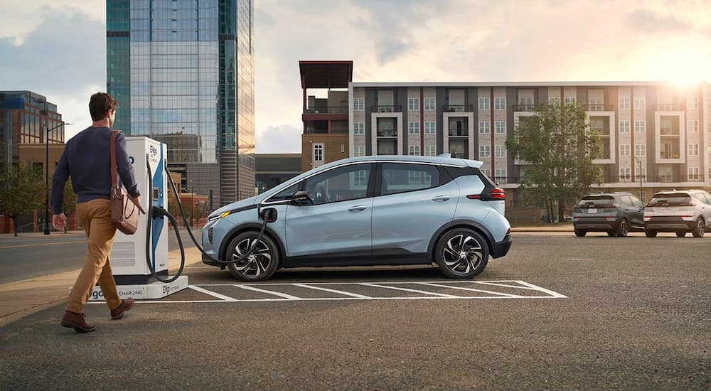 A popular Chevy EV, a pale blue 2022 Chevy Bolt EV, is shown from the side at a charging station in a city.