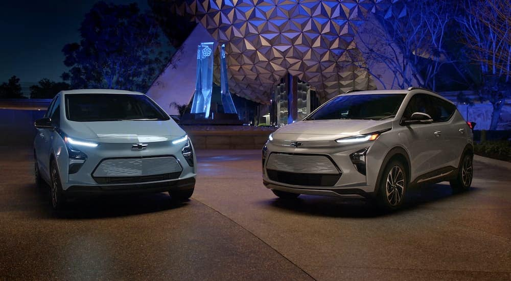 A pale blue 2022 Chevy Bolt EV is parked next to a tan EUV in front of a geodesic dome.