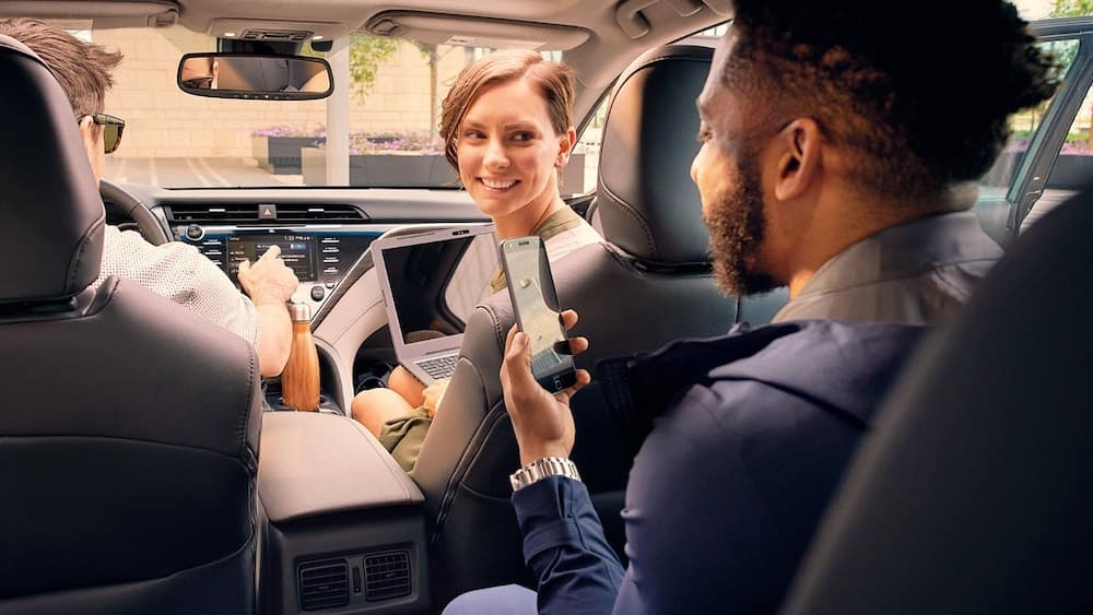 2019 Toyota Camry with man on smartphone using Toyota Remote Connect