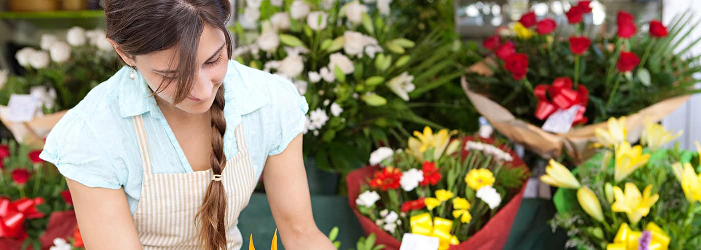 Close up portrait of a young professional small business owner businesswoman florist arranging and tendering her flowers, plants and stock, working in her fresh flowers store, outdoors.