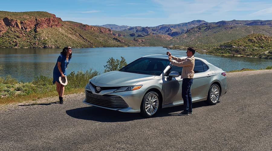 couple taking photos next to camry