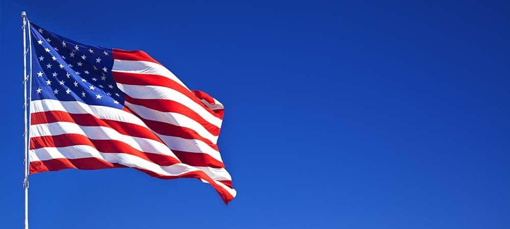 American flag waving in blue sky