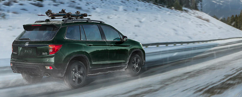 Green 2019 Honda Pilot travels up hilly snowy road
