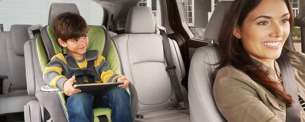 Child in car seat on table in Honda Odyssey with mom driving and smiling