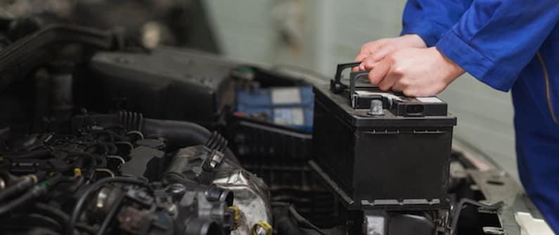 Technician replacing a car battery