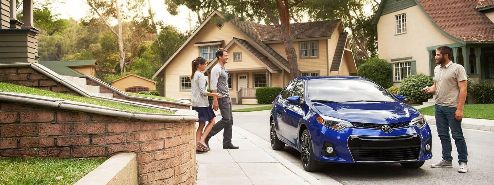 couple walks to Toyota Corolla while man is standing near driver's door