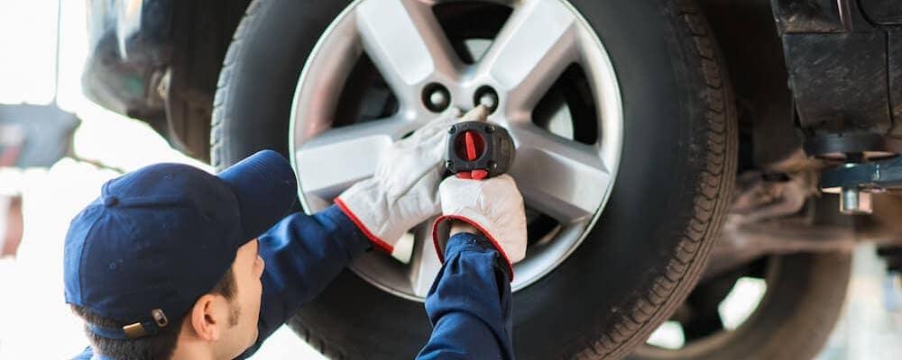 Technician replacing a tire.