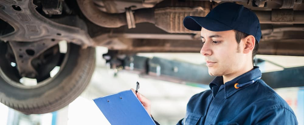 Portrait of a mechanic taking notes under a car