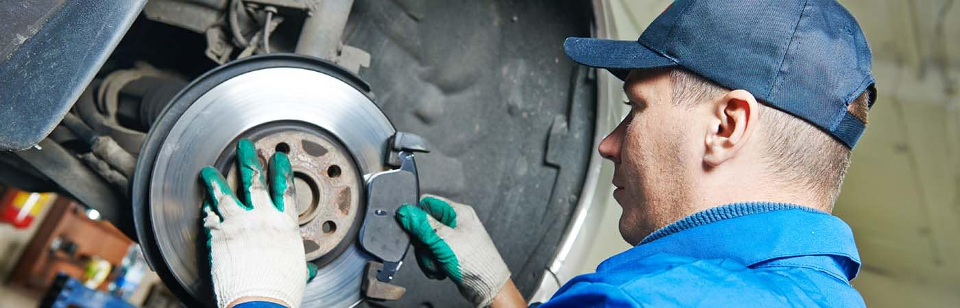 car mechanic worker replacing brakes of lifted automobile at auto repair garage