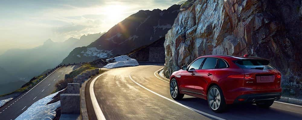 red 2019 jaguar f-pace driving on mountain highway