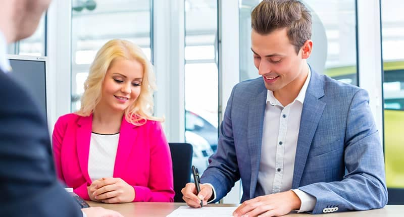 Couple Signing Car Buying Documents