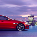 Red Jaguar XE against city skyline