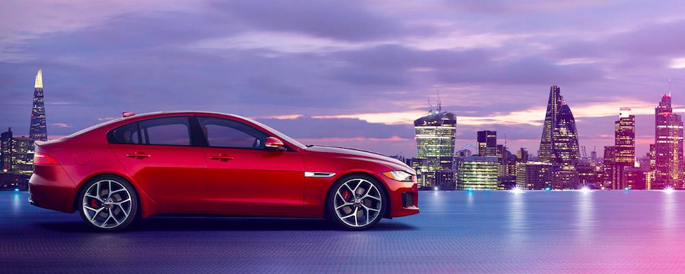 Red Jaguar XE against city skyline