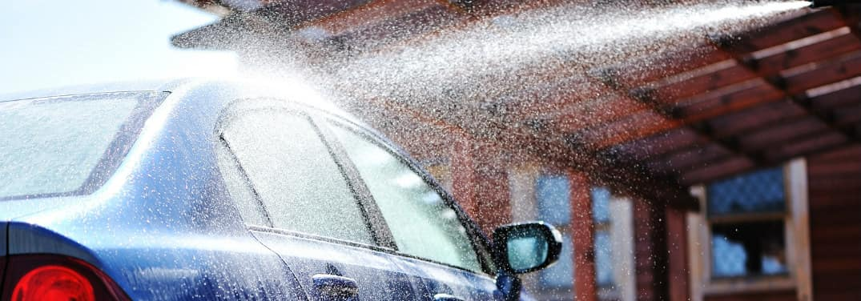 washing a blue car with a pressured hose