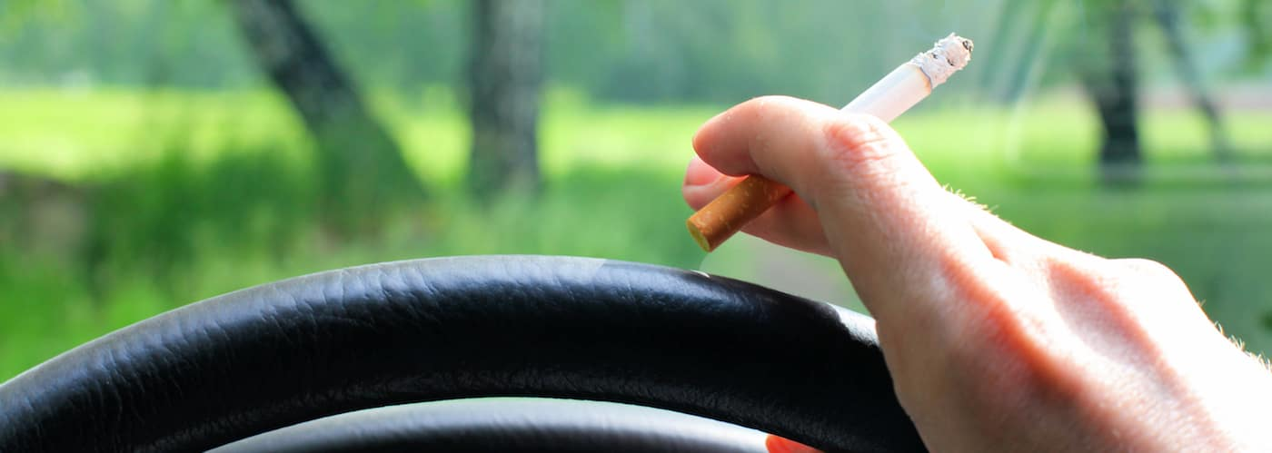 Hand holding cigarette near steering wheel