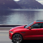 Red 2021 F-PACE driving near body of water