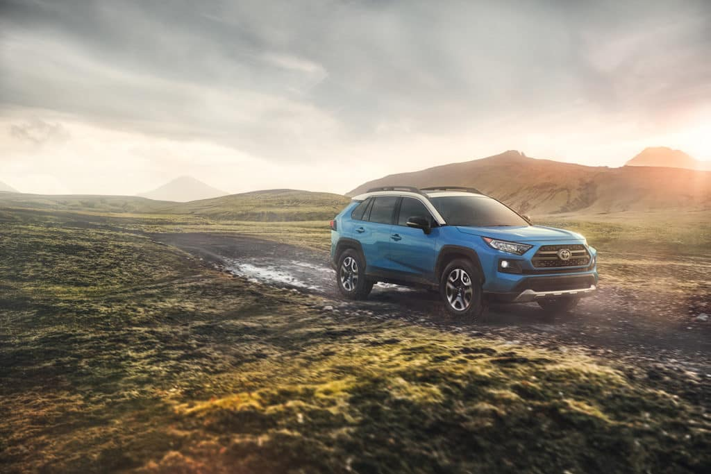 Blue 2019 RAV4 driving through the highlands