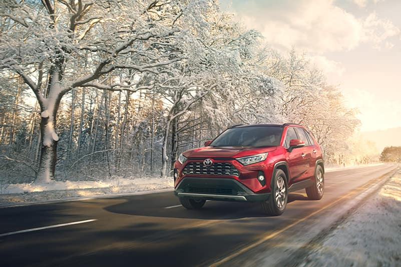 Comparison of the Toyota RAV4 and the Honda CR-V crossovers at Lancaster Toyota | Red 2019 RAV4 running on road in the winter