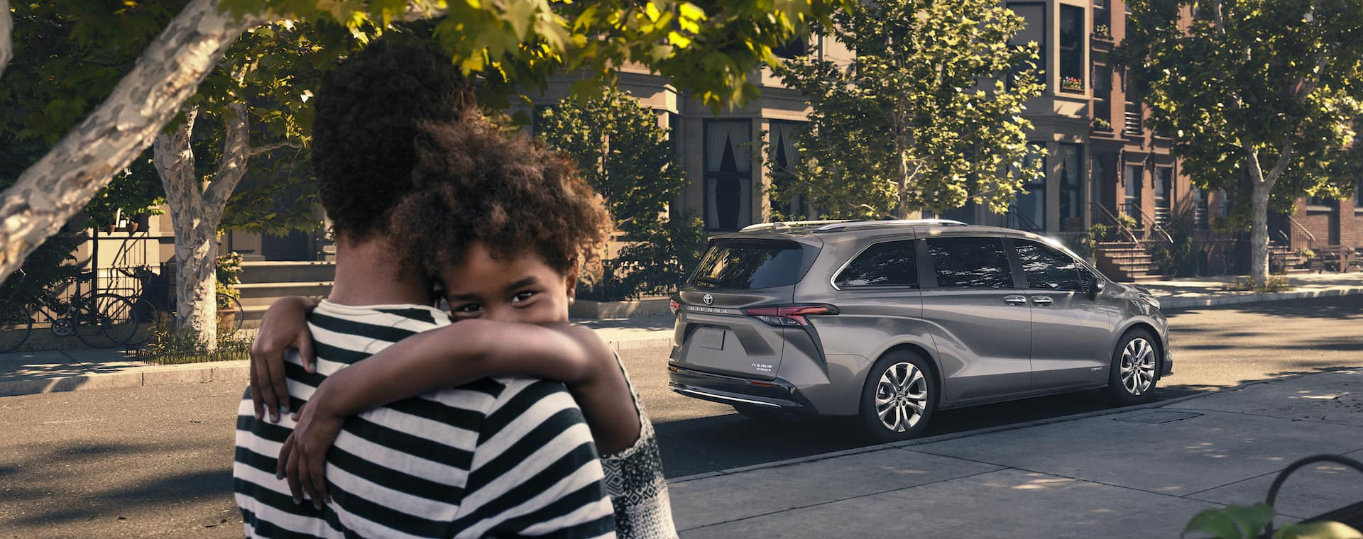 Compare the Toyota Sienna with the Honda Odyssey at Lancaster Toyota of East Petersburg | Father holding young daughter with view of 2021 Toyota Sienna in background