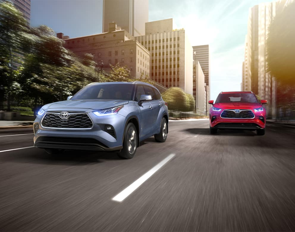 Lancaster Toyota is a Car Dealership in Lancaster near York PA   Blue 2020 Highlander and Red 2020 Highlander Hybrid Driving Side by Side Through City