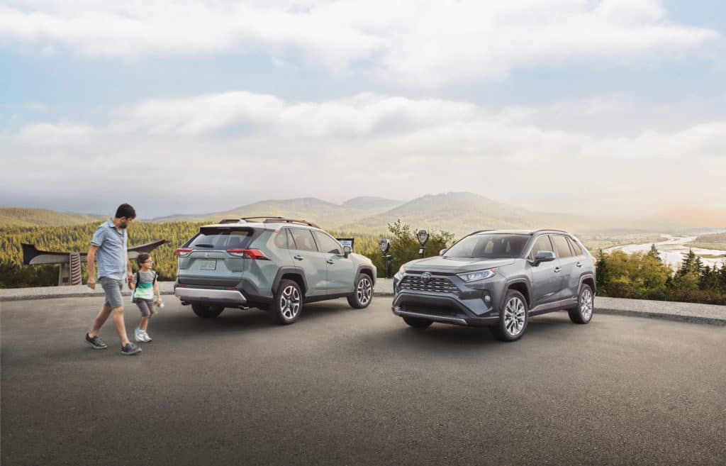 Lancaster Toyota is a Car Dealership in Lancaster near Farmdale, PA | Father and child walking by 2020 Toyota RAV4 vehicles parked by scenic overlook
