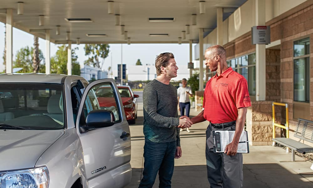 Lancaster Toyota is a Toyota Dealership in Lancaster near Mountville, PA | Customer and Toyota Sales Advisor Shaking Hands Next to Tacoma