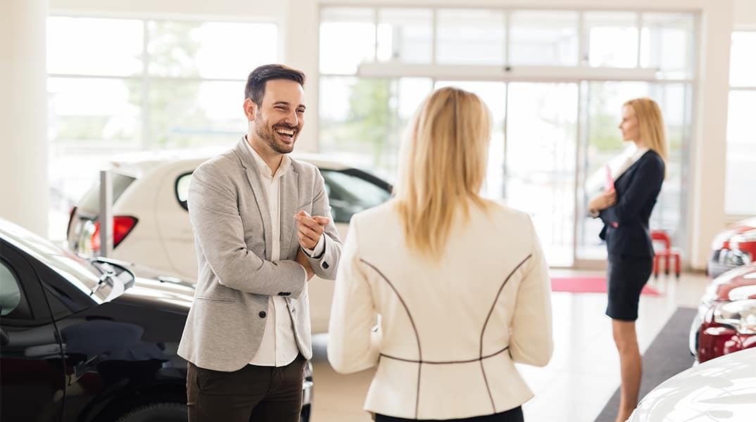 Lancaster Toyota is a Car Dealership in Lancaster near Cornwall PA | Customer and Sales Advisor Talking While in Vehicle Showroom