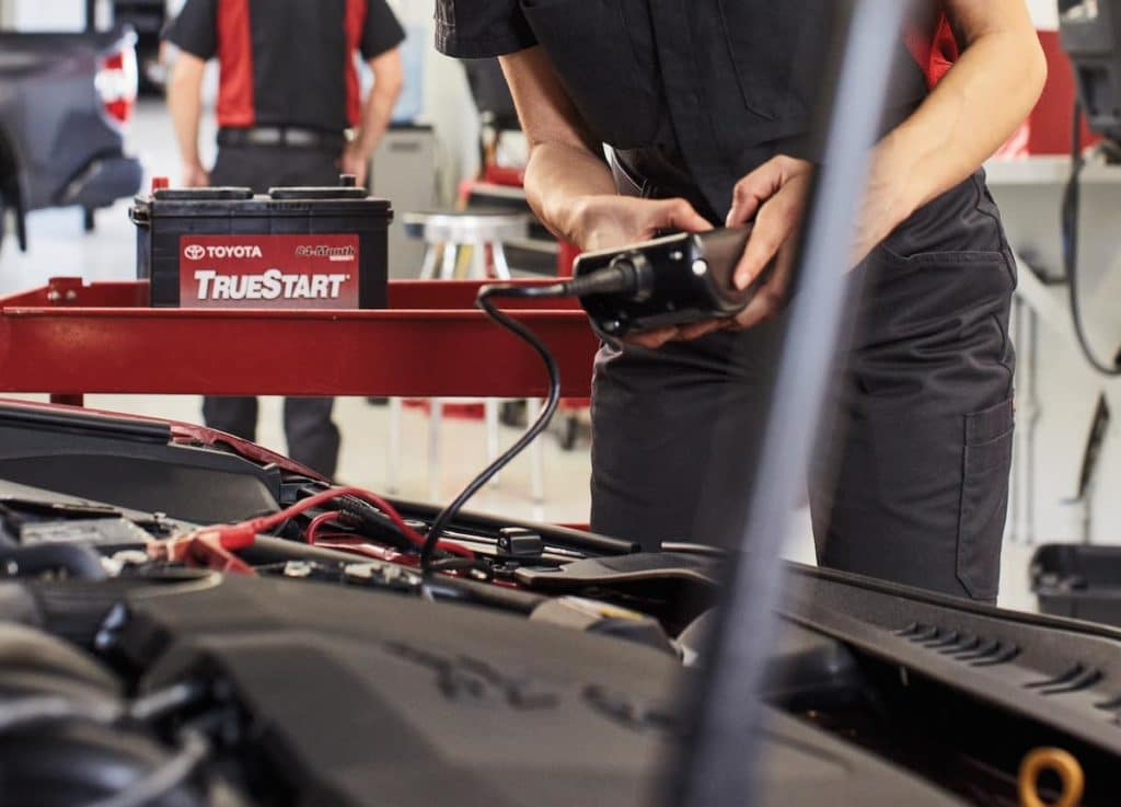 Lancaster Toyota is a Car Dealership in Lancaster near Farmdale, PA | Toyota service technician checking battery on Toyota vehicle