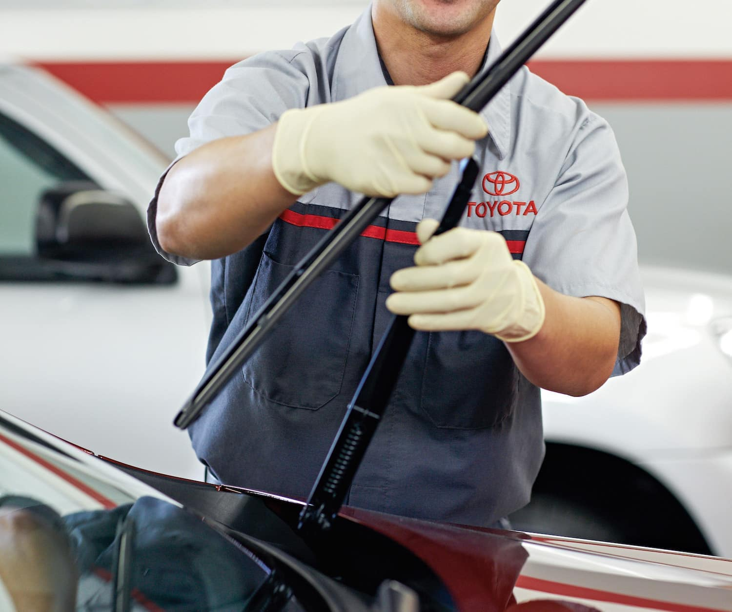 Lancaster Toyota is a Toyota Dealer Near Lancaster PA | Toyota Service Advisor Replacing Windshield Wiper On Red Toyota Vehicle