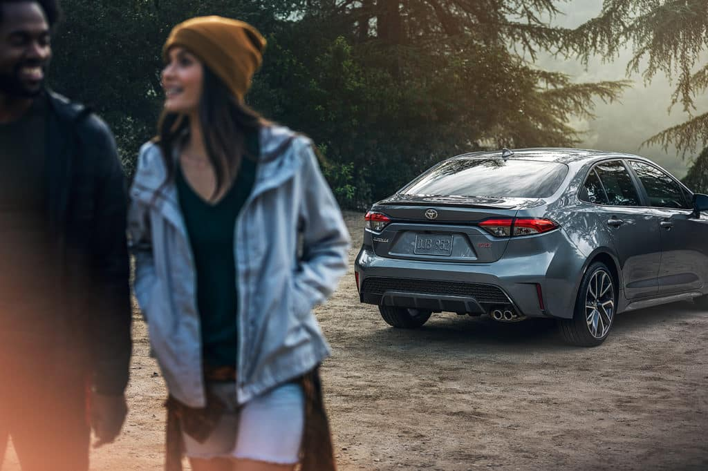 Lancaster Toyota is a Car Dealership in Lancaster near Farmdale, PA | Man and woman walking away from 2020 Toyota Corolla parked in the woods