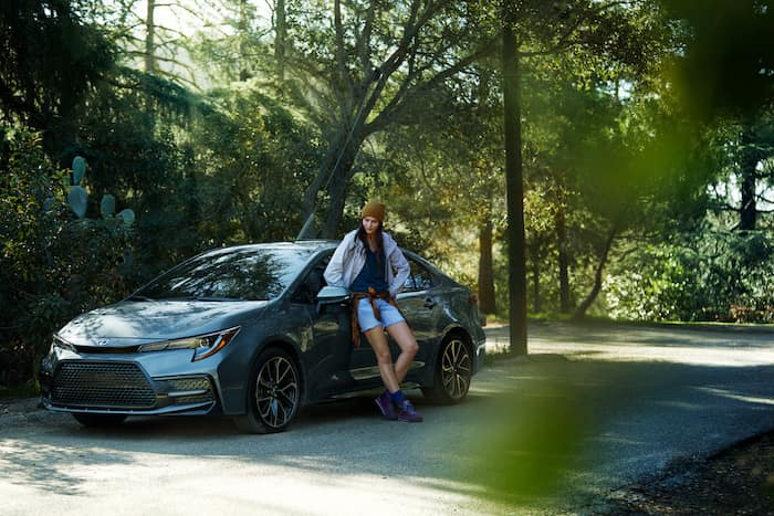 Compare the 2020 Honda Civic Sedan vs. the 2020 Toyota Corolla at Lancaster Toyota of East Petersburg | woman leaning on the corolla