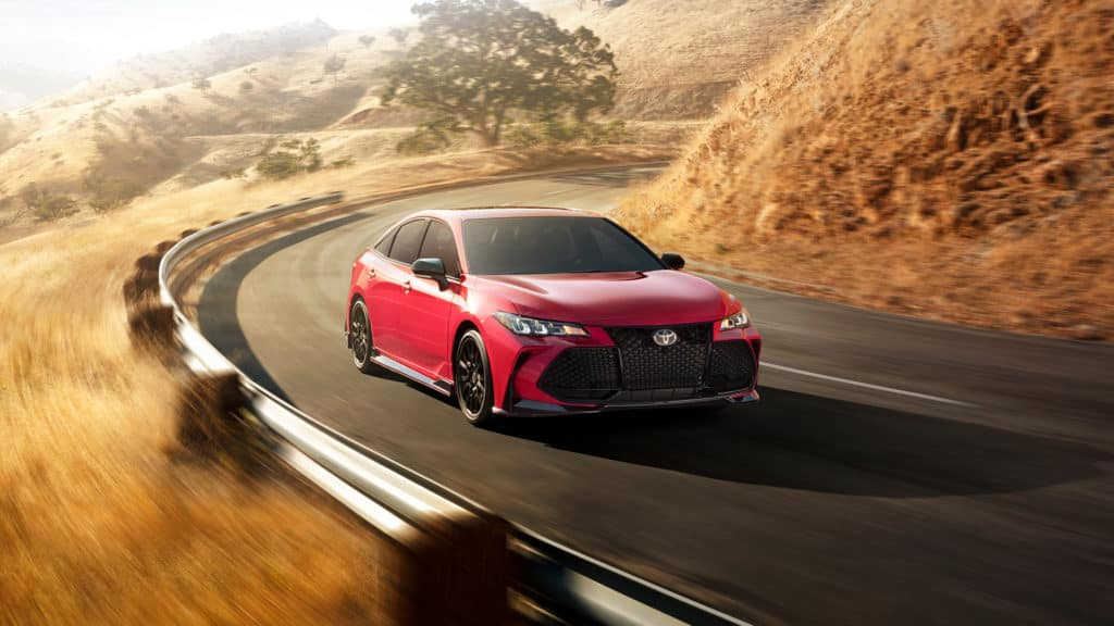 Lancaster Toyota is a Car Dealership in Lancaster near Roherstown, PA | Red 2020 Toyota Avalon driving on country road