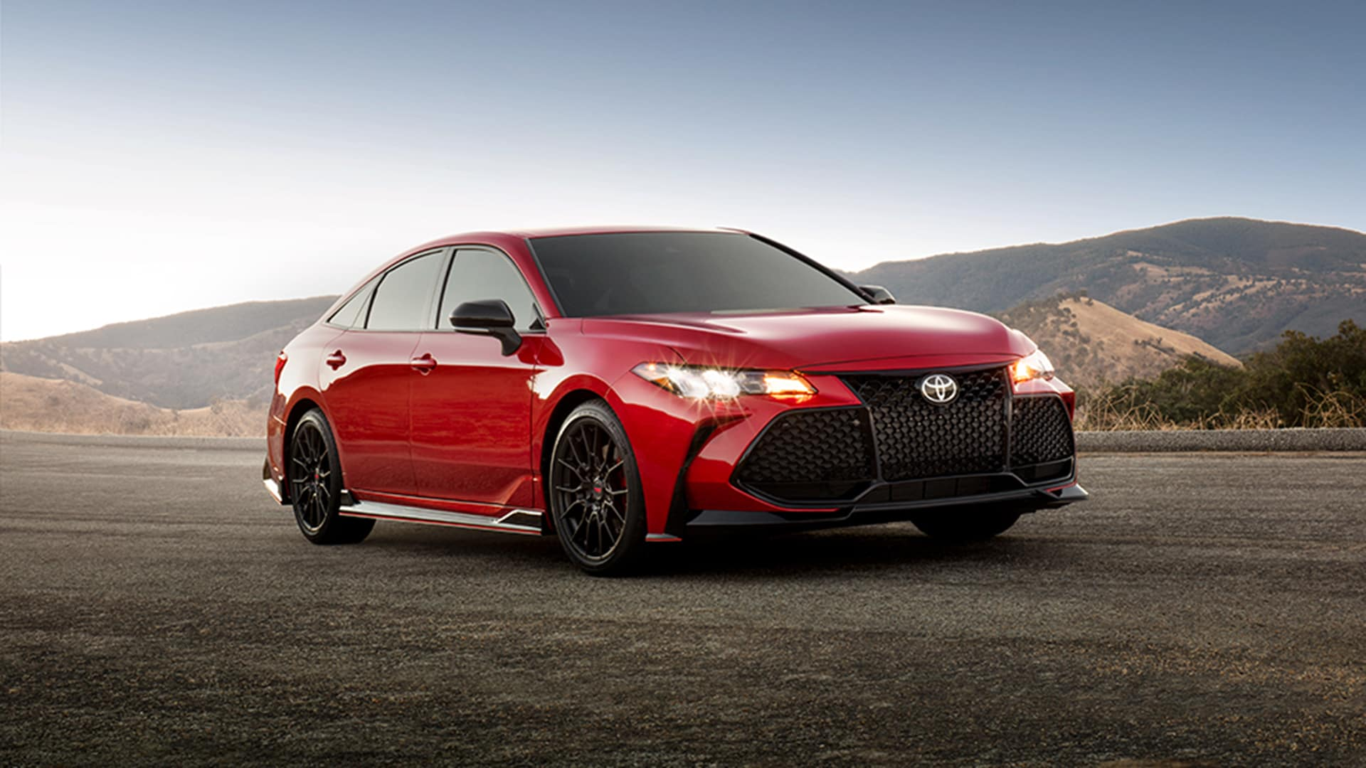 Lancaster Toyota is a new and used Car Dealer near Elizabethtown, PA | Red MY20 Toyota Avalon parked on road in front of mountains