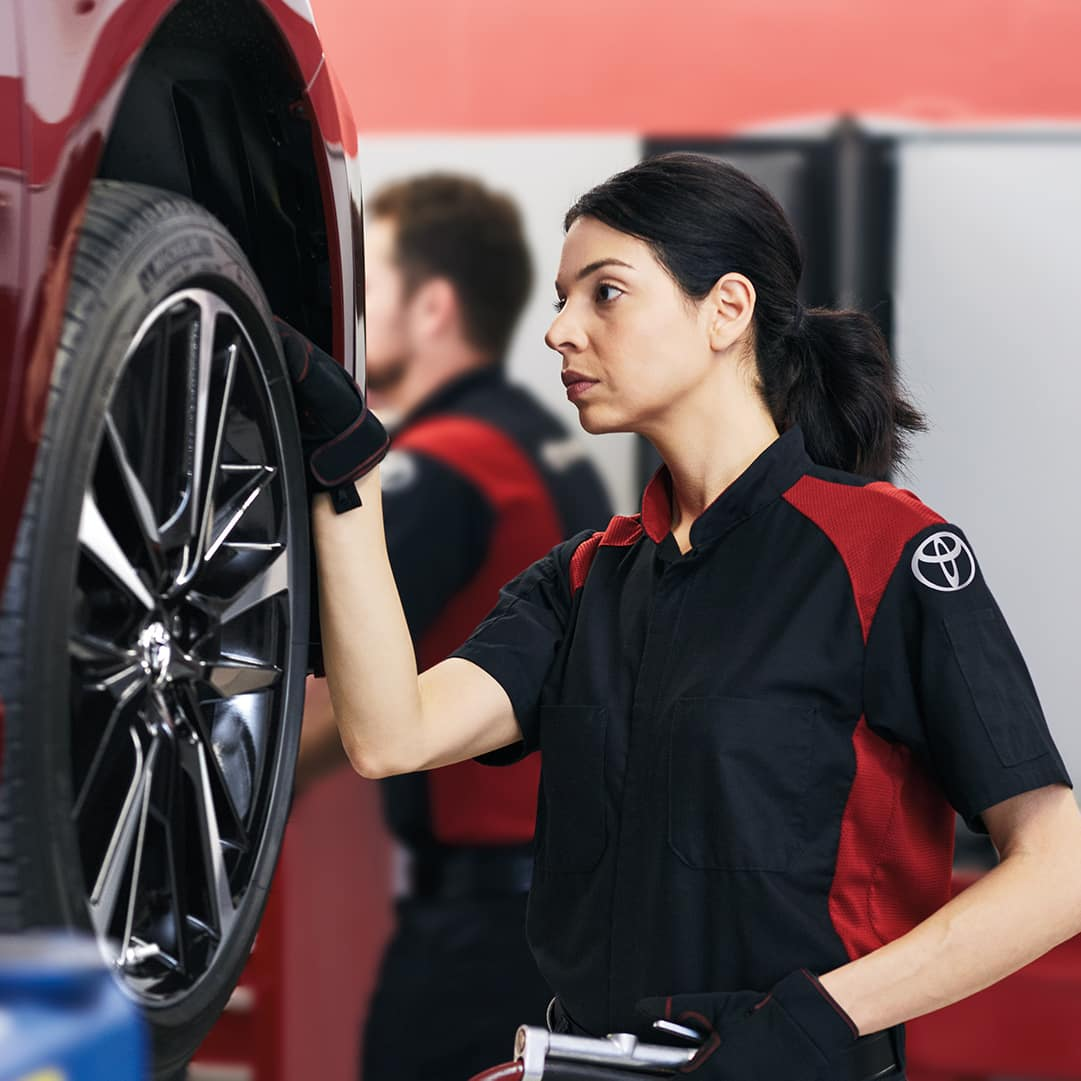Lancaster Toyota is a new and used Car Dealer near Elizabethtown, PA | Lady Toyota mechanic checking tire
