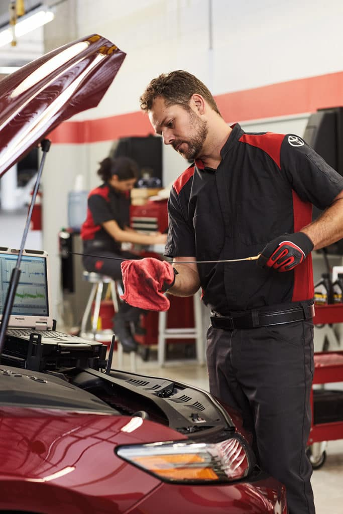 Lancaster Toyota is a Car Dealership in Lancaster near Farmdale, PA | Toyota service technician checking oil level on Toyota vehicle