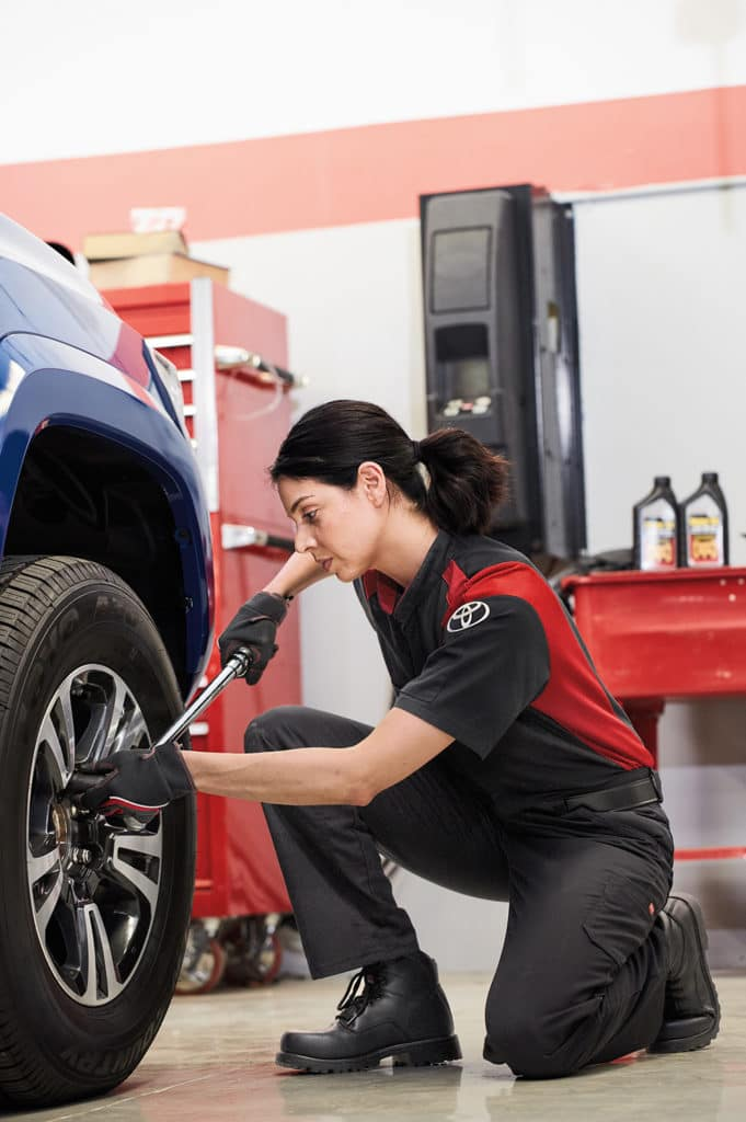 Lancaster Toyota is a Car Dealership in Lancaster near Roherstown, PA | Toyota Service Advisor replacing wheel on Toyota vehicle