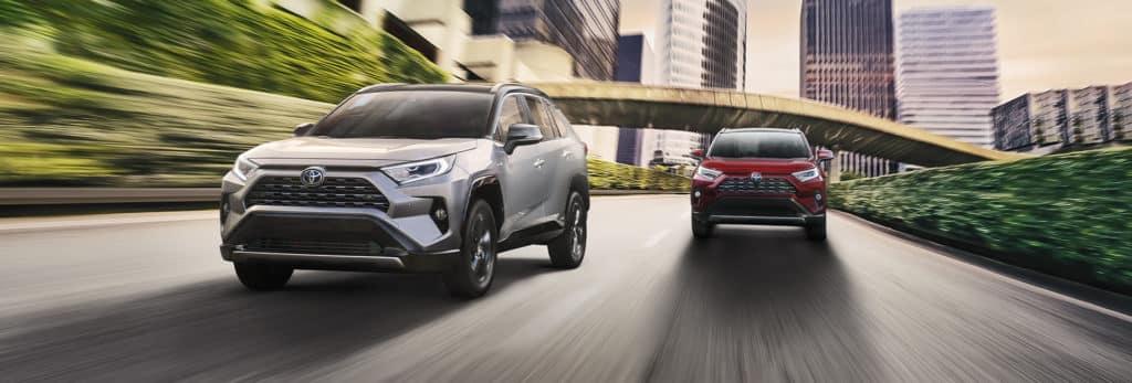 Compare the 2021 Toyota RAV4 Hybrid vs. the Honda CR-V Hybrid crossovers at Lancaster Toyota | Two RAV4 Hybrids speeding on highway