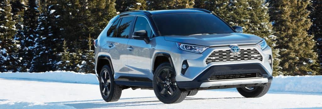 Compare the 2021 Toyota RAV4 Hybrid vs. the Honda CR-V Hybrid crossovers at Lancaster Toyota | RAV4 Hybrid on snowy road