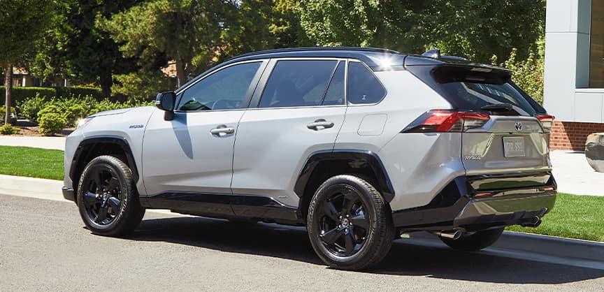 Compare the 2021 Toyota RAV4 Hybrid vs. the Honda CR-V Hybrid crossovers at Lancaster Toyota | 2021 RAV4 parked outside modern home