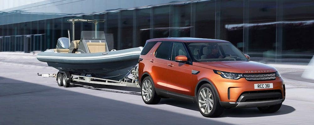 2019 Land Rover Discovery in orange towing a boat