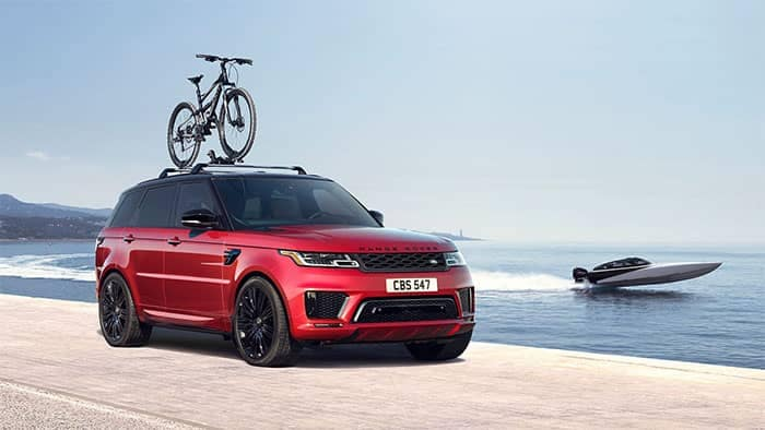 Range Rover Sport by waterfront with bikes on roof rack