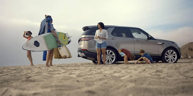 Family standing by Land Rover Discovery on the beach