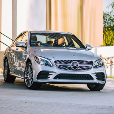 A look at the front of a shiny silver 2019 Mercedes-Benz C-Class sedan parked in the concrete driveway of a classy upscale building as sunlight shines through the driver's window