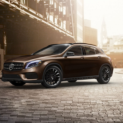 The front driver side of a shiny dark bronze 2019 Mercedes-Benz GLA SUV turning down a bricked road under a bridge in a port city at sunset
