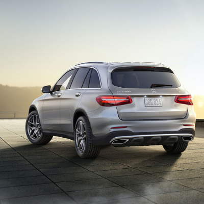 The back angle of a silver 2019 Mercedes-Benz GLC SUV parked on a tiled platform overlooking a mountain range with the sun setting behind the mountains