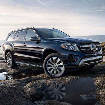 A front passenger side angle of a dark blue 2019 Mercedes-Benz GLE SUV as it drives over a rocky wet shoreline off the ocean with a cloudy sky in the background as the sun starts to rise