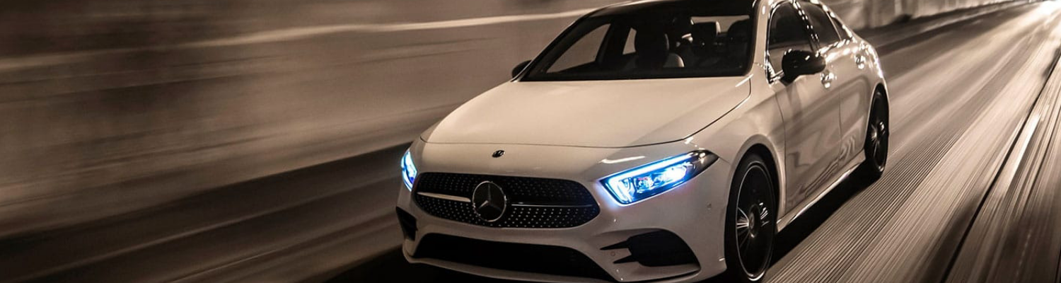 Front driver side angle of a white 2019 Mercedes A-Class sedan driving through a tunnel underpass with blurred road lines