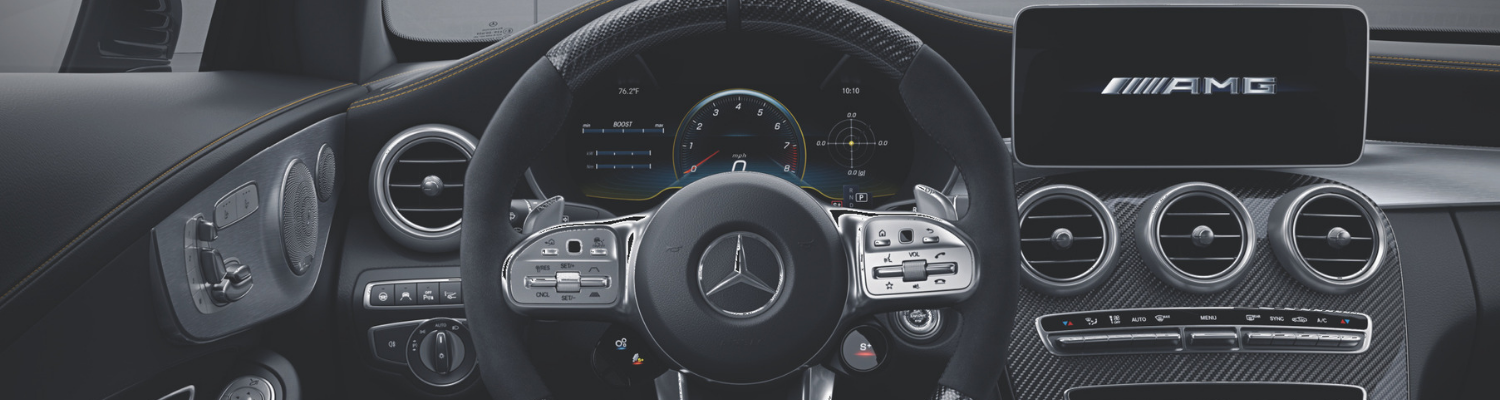 Interior of a 2019 Mercedes C-Class AMG lxury sedan showing a sleek design with a carbon fiber look and touch screen display