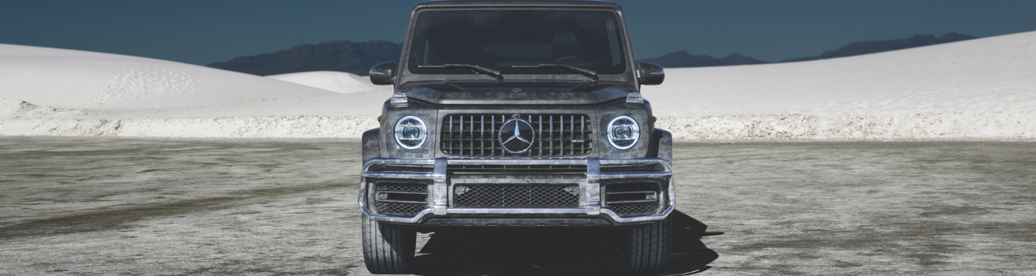 Front hood level view of a new 2019 Mercedes G-Class SUV parked on a snowy mound in Colorado Springs