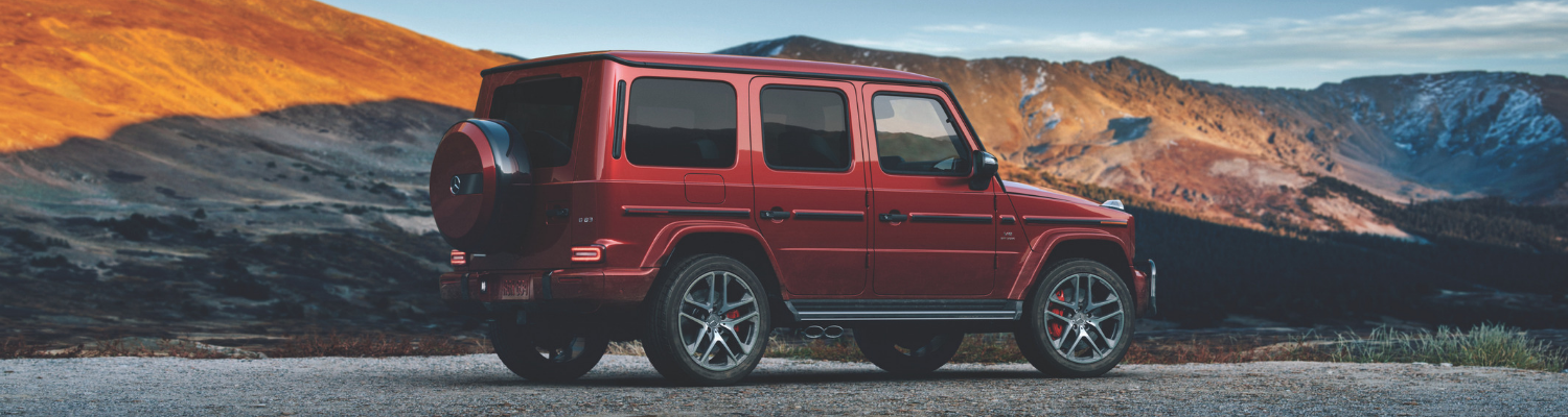 Rear passenger side angle of a red 2019 Mercedes G-Class luxury SUV parked in between mountain ranges as the sun sets casting a shadow